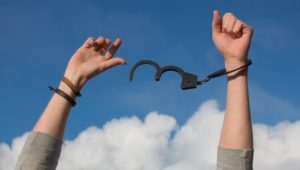hands freeing themselves from handcuffs