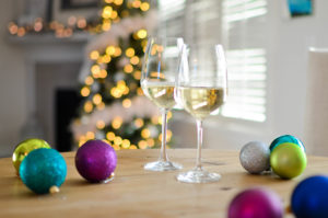 glasses of white wine sitting on a table with holiday ornaments and decor