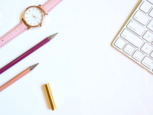 desktop featuring colorful pencils and a watch