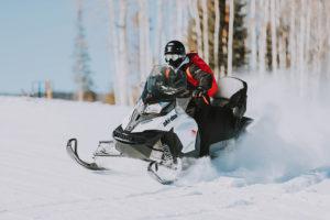 snowmobile riding across a snowy meadow