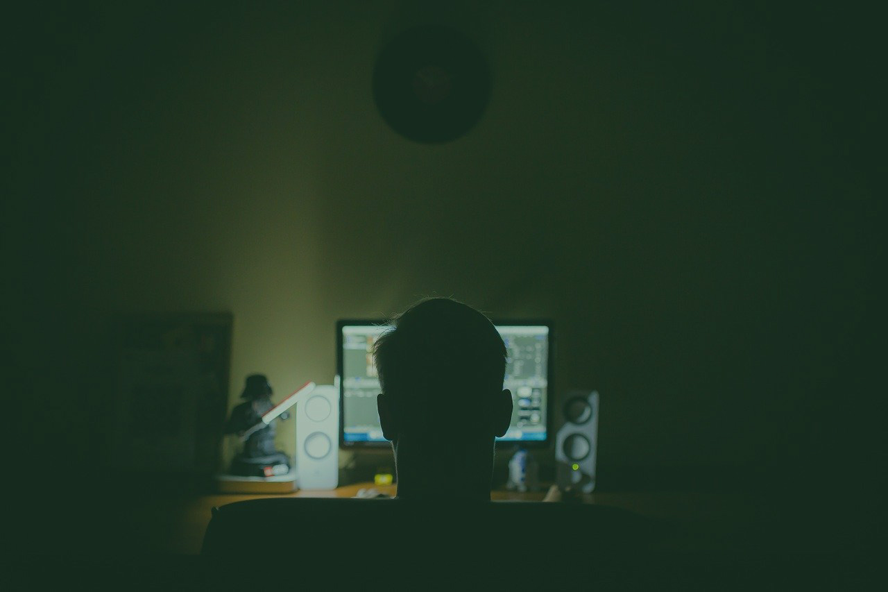 man sitting in the dark on his computer