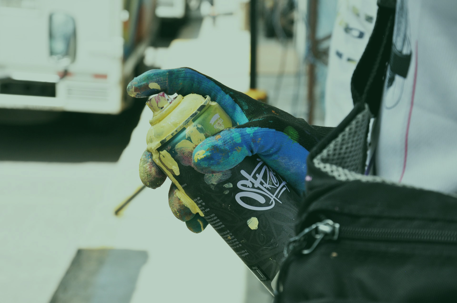 gloved hand holding a can of yellow spray paint