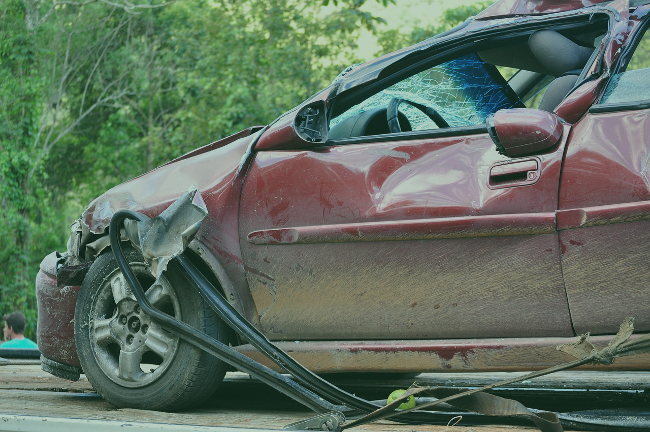 maroon car with significant damage sitting on a flat bed truck
