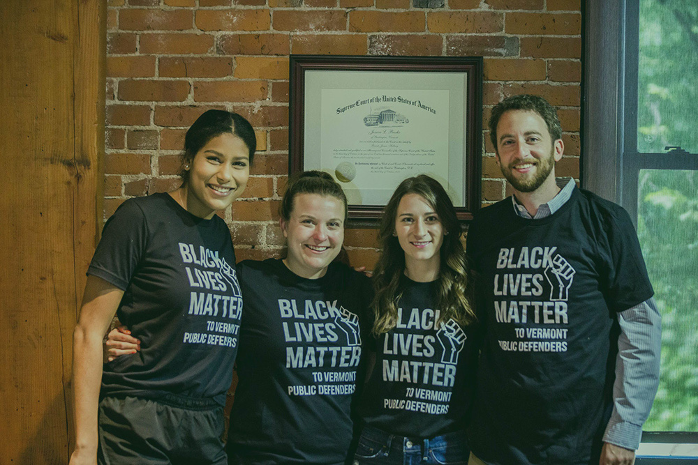 burke law team wearing black lives matter t-shirts with an exposed brick wall as the backdrop